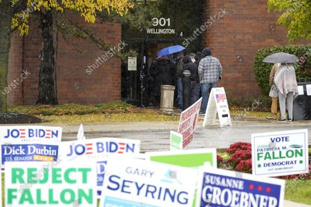 People wait in line during early voting at Elk Grove Village Hall in Elk Grove Village, Ill., . The US early voting total in 2020 has already exceeded the number of early votes cast in 2016 and there are still 11 more days to go until Election Day