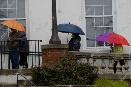 People hold their umbrella as they wait in line during early voting at Park Ridge City Hall in Park Ridge, Ill., . The US early voting total in 2020 has already exceeded the number of early votes cast in 2016 and there are still 11 more days to go until Election Day