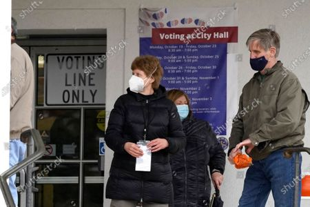 People wear masks as they wait in line during early voting at Park Ridge City Hall in Park Ridge, Ill., . The US early voting total in 2020 has already exceeded the number of early votes cast in 2016 and there are still 11 more days to go until Election Day