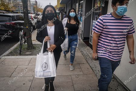 "Emili Prado, 21, left, legal liaison for La Colmena, a community-based organization working with immigrant workers, walk with volunteers Christine Cuenca, 18, center, and Jason Jimenez, 19, right, to deliver information local business in a campaign to turn out the vote in the largely Hispanic community of Port Richmond in Staten Island, N.Y., . Prado, a DACA recipient who is studying to become a lawyer, said ""This campaign is very important for me, we are including our youth who can vote for the very first time and they are the voice of us who cannot vote"