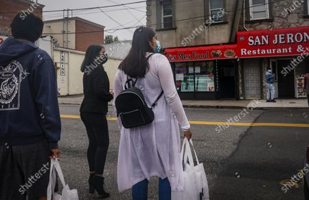 "Emili Prado, 21, center, legal liaison for La Colmena, a community-based organization working with immigrant workers, and volunteers Christine Cuenca, 18, right, Johnny Basurto, 20, left, carry bags of flyers for local businesses in a campaign to turn out the vote in the largely Hispanic community of Port Richmond in Staten Island, N.Y., . Prado, a DACA recipient who is studying to become a lawyer, said ""This campaign is very important for me, we are including our youth who can vote for the very first time and they are the voice of us who cannot vote"