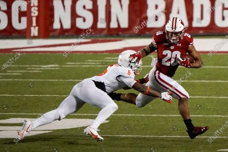 Stock Photo of Wisconsin running back Isaac Guerendo tries to get away from Illinois defensive back Tony Adams during the second half of an NCAA college football game, in Madison, Wis. Wisconsin won 45-7