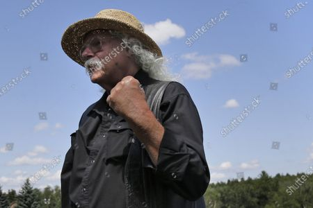 Arlo Guthrie reacts after playing a song at the original site of the 1969 Woodstock Music and Arts Fair in Bethel, N.Y. In lengthy posts on his Facebook page and website, the 73-year-old folksinger announced, he is retiring from performance immediately. He's canceled numerous shows next year and says he won't book any new ones