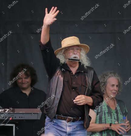 Arlo Guthrie waves to the crowd during a concert at a Woodstock 50th anniversary event in Bethel, N.Y. In lengthy posts on his Facebook page and website, the 73-year-old folksinger announced, he is retiring from performance immediately. He's canceled numerous shows next year and says he won't book any new ones