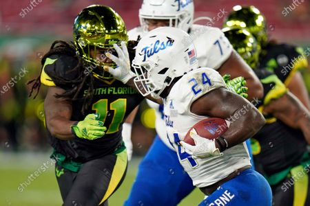 Tulsa running back Corey Taylor II (24) stiff arms South Florida linebacker Dwayne Boyles Jr. (11) on a run during the first half of an NCAA college football game, in Tampa, Fla