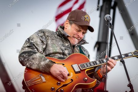 Stock Image of Musical artist Ted Nugent plays the American national anthem before U.S. President Donald Trump speaks at an outdoor rally at Muskegon County Airport in Norton Shores, Michigan