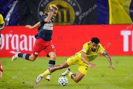 New England Revolution forward Diego Fagundez, left, and Nashville SC midfielder Anibal Godoy, right, collide during the first half of an MLS soccer match, in Nashville, Tenn