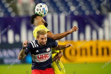Nashville SC midfielder Anibal Godoy, top, heads the ball away from New England Revolution forward Diego Fagundez during the first half of an MLS soccer match, in Nashville, Tenn