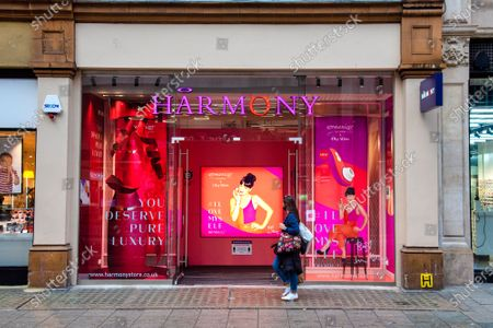 """A woman walks past a window display advertisement at the Harmony Sex Shop in London's Oxford Street for Pop star Lily Allen's """"Liberty"""" sex toy collaboration with Womanizer."""