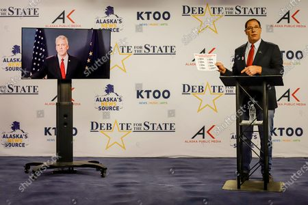 Al Gross, right, an independent in Alaska's U.S. Senate race, holds a document during a debate with Republican U.S. Sen. Dan Sullivan, in Anchorage, Alaska. Sullivan participated remotely, as the Senate prepares to vote on President Donald Trump's Supreme Court nominee in Washington