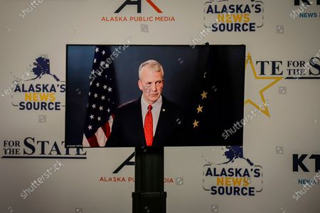 Republican U.S. Sen. Dan Sullivan shown in a monitor looks on during a debate with his major rival in Alaska's Senate race, in Anchorage, Alaska. Sullivan participated in the debate against independent Al Gross remotely, as the Senate prepares to vote on President Donald Trump's Supreme Court nominee in Washington