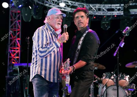 Mike Love, left, of The Beach Boys, performs with guest member John Stamos during the Concerts In Your Car series at the Ventura County Fairgrounds, in Ventura, Calif