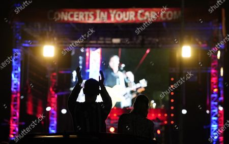 Fans are silhouetted as they watch The Beach Boys perform during the Concerts In Your Car series at the Ventura County Fairgrounds, in Ventura, Calif