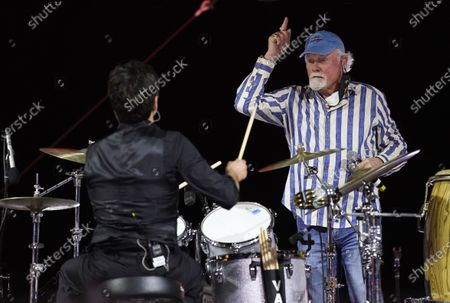 Mike Love of The Beach Boys, right, performs with guest member John Stamos on drums during the Concerts In Your Car series at the Ventura County Fairgrounds, in Ventura, Calif