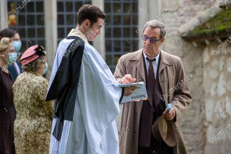 Robson Green (brown coat)  and Tom Brittney (vicar) filming the ITV drama Grantchester in the village of Grantchester near Cambridge on Monday afternoon. Comedian Miles Jupp had actor Robson Green in stitches on the set of ITV's crime drama Grantchester yesterday (Mon).The 41-year-old, who is guest starring in the latest season of the 1950s series, was spotted laughing with the actor in between takes during filming in the picturesque village of Grantchester in Cambridgeshire.Jupp, who is well known for his stand-up, was dressed in a smart blue suit and sported greying hair for his part in the programme. Robson Green, who is reprising his role as DI Geordie Keating, wore his trademark beige overcoat.Earlier in the day Jupp's character was seen getting into a fight with another male character and had to be held back by actor Tom Brittney, who plays Reverend Will Davenport.The actors and film crew were all seen to be abiding by strict rules to prevent the spread of coronavirus on set, with a poster of instructions up and masks worn.Other guest stars this season will include Jemma Redgrave, Gary Beadle (who plays the Archdeacon), Rachael Stirling and and Rebecca Front.New instalments will be set in 1958, with the unlikely crime-fighting duo solving yet more cases. The first episode will see the pair attempting to unwind during a holiday camp Ð only to end up investigating a murder at the resort.In a statement, Kudos Executive Producer Emma Kingsman-Lloyd said: ÒIn these difficult times we are delighted to be able to film another series of our beloved Grantchester.ÒThe cast and crew have worked tirelessly to bring the series to the screen and we know the audience are very excited to see what Will, Geordie and the Grantchester family have in store for them.ÓThe series is adapted from the Grantchester Mysteries novels by James Runcie and was developed for television by Daisy Coulam.
