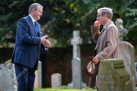 Robson Green (brown coat) and Miles Jupp, (blue suit) sharing a joke in a break during the filming of the ITV drama Grantchester in the village of Grantchester near Cambridge on Monday afternoon. Comedian Miles Jupp had actor Robson Green in stitches on the set of ITV's crime drama Grantchester yesterday (Mon).The 41-year-old, who is guest starring in the latest season of the 1950s series, was spotted laughing with the actor in between takes during filming in the picturesque village of Grantchester in Cambridgeshire.Jupp, who is well known for his stand-up, was dressed in a smart blue suit and sported greying hair for his part in the programme. Robson Green, who is reprising his role as DI Geordie Keating, wore his trademark beige overcoat.Earlier in the day Jupp's character was seen getting into a fight with another male character and had to be held back by actor Tom Brittney, who plays Reverend Will Davenport.The actors and film crew were all seen to be abiding by strict rules to prevent the spread of coronavirus on set, with a poster of instructions up and masks worn.Other guest stars this season will include Jemma Redgrave, Gary Beadle (who plays the Archdeacon), Rachael Stirling and and Rebecca Front.New instalments will be set in 1958, with the unlikely crime-fighting duo solving yet more cases. The first episode will see the pair attempting to unwind during a holiday camp Ð only to end up investigating a murder at the resort.In a statement, Kudos Executive Producer Emma Kingsman-Lloyd said: ÒIn these difficult times we are delighted to be able to film another series of our beloved Grantchester.ÒThe cast and crew have worked tirelessly to bring the series to the screen and we know the audience are very excited to see what Will, Geordie and the Grantchester family have in store for them.ÓThe series is adapted from the Grantchester Mysteries novels by James Runcie and was developed for television by Daisy Coulam.