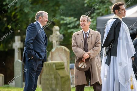 Robson Green (brown coat) ,Miles Jupp, (blue suit) and Tom Brittney (vicar) filming the ITV drama Grantchester in the village of Grantchester near Cambridge on Monday afternoon. Comedian Miles Jupp had actor Robson Green in stitches on the set of ITV's crime drama Grantchester yesterday (Mon).The 41-year-old, who is guest starring in the latest season of the 1950s series, was spotted laughing with the actor in between takes during filming in the picturesque village of Grantchester in Cambridgeshire.Jupp, who is well known for his stand-up, was dressed in a smart blue suit and sported greying hair for his part in the programme. Robson Green, who is reprising his role as DI Geordie Keating, wore his trademark beige overcoat.Earlier in the day Jupp's character was seen getting into a fight with another male character and had to be held back by actor Tom Brittney, who plays Reverend Will Davenport.The actors and film crew were all seen to be abiding by strict rules to prevent the spread of coronavirus on set, with a poster of instructions up and masks worn.Other guest stars this season will include Jemma Redgrave, Gary Beadle (who plays the Archdeacon), Rachael Stirling and and Rebecca Front.New instalments will be set in 1958, with the unlikely crime-fighting duo solving yet more cases. The first episode will see the pair attempting to unwind during a holiday camp Ð only to end up investigating a murder at the resort.In a statement, Kudos Executive Producer Emma Kingsman-Lloyd said: ÒIn these difficult times we are delighted to be able to film another series of our beloved Grantchester.ÒThe cast and crew have worked tirelessly to bring the series to the screen and we know the audience are very excited to see what Will, Geordie and the Grantchester family have in store for them.ÓThe series is adapted from the Grantchester Mysteries novels by James Runcie and was developed for television by Daisy Coulam.