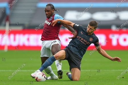 West Ham's Michail Antonio challenges Manchester City's Ruben Dias, right, during the English Premier League soccer match between West Ham and Manchester City, at the London Olympic Stadium