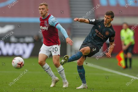 Manchester City's Ruben Dias passes the ball past West Ham's Jarrod Bowen during the English Premier League soccer match between West Ham and Manchester City, at the London Olympic Stadium