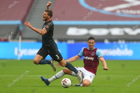Stock Photo of Manchester City's Ruben Dias is tackled by West Ham's Fabian Balbuena during the English Premier League soccer match between West Ham and Manchester City, at the London Olympic Stadium