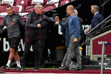 West Ham's manager David Moyes, 2nd left, and Manchester City's head coach Pep Guardiola greet each other prior to the English Premier League soccer match between West Ham and Manchester City, at the London Olympic Stadium
