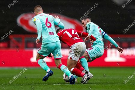 Andreas Weimann of Bristol City is tackled by Jay Fulton and Matt Grimes of Swansea City