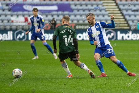 Wigan Athletic defender Tom James (27) tackles Plymouth Argyle midfielder Ben Reeves (14) during the EFL Sky Bet League 1 match between Wigan Athletic and Plymouth Argyle at the DW Stadium, Wigan