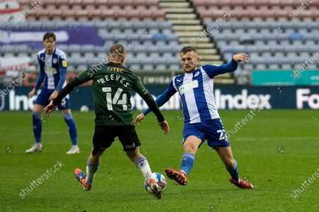 Stock Image of Wigan Athletic defender Tom James (27) tackles Plymouth Argyle midfielder Ben Reeves (14) during the EFL Sky Bet League 1 match between Wigan Athletic and Plymouth Argyle at the DW Stadium, Wigan