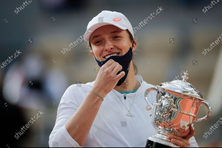 Stock Picture of Poland's Iga Swiatek holds the trophy after winning the final match of the French Open tennis tournament against Sofia Kenin of the U.S. in two sets 6-4, 6-1, at the Roland Garros stadium in Paris, France. French Open champion Iga Swiatek said she will quarantine after meeting with Poland President Andrzej Duda. Duda's office announced Saturday, Oct. 24, 2020 that he tested positive for coronavirus. The 19-year-old Swiatek met with Duda on Friday