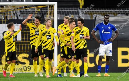 Dortmund's Mats Hummels, left, celebrates his side's third goal beside disappointed Schalke's Salif Sane, right, during the German Bundesliga soccer match between Borussia Dortmund and FC Schalke 04 in Dortmund, Germany