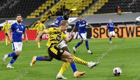 Dortmund's Erling Haaland shots on goal in front of Schalke's Salif Sane during the German Bundesliga soccer match between Borussia Dortmund and FC Schalke 04 in Dortmund, Germany