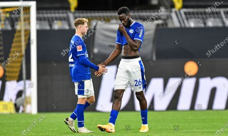 Schalke's Salif Sane, right, and teammate Kilian Ludewig leave the pitch disappointed after the German Bundesliga soccer match between Borussia Dortmund and FC Schalke 04 in Dortmund, Germany
