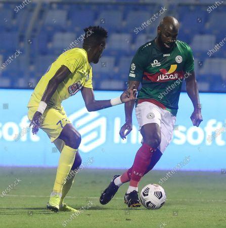 Al-Ettifaq player Souleymane Doukara (R) in action against Al-Ain player Hassan Al-Harbi (L) during the Saudi Professional League soccer match between Al-Ittifaq and Al-Ain at Prince Mohamed bin Fahd Stadium, in Dammam, Saudi Arabia, 24 October 2020.