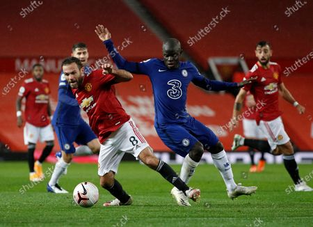Manchester United's Juan Mata, left, duels for the ball with Chelsea's N'Golo Kante during the English Premier League soccer match between Manchester United and Chelsea, at the Old Trafford stadium in Manchester, England