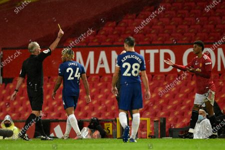 Referee Martin Atkinson, left, shows a yellow card to Manchester United's Marcus Rashford, right, during the English Premier League soccer match between Manchester United and Chelsea, at the Old Trafford stadium in Manchester, England