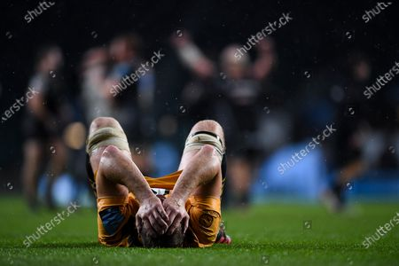 Exeter Chiefs celebates as the final whistle is blown as Joe Launchbury of Wasps is dejected as he holds his head after the final whistle of the match