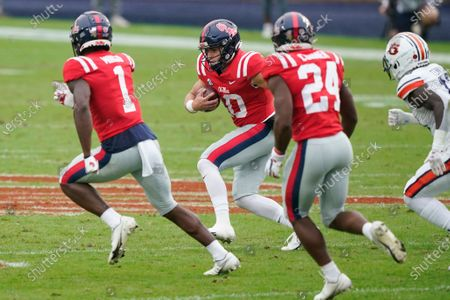 Mississippi quarterback John Rhys Plumlee (10) follows his blockers wide receiver Jonathan Mingo (1) and running back Snoop Conner (24) as he runs past Auburn defenders during the first half of an NCAA college football game in Oxford, Miss
