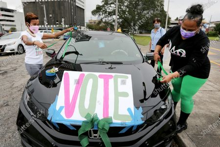 """Maurya Glaude and Angela Davis decorate a car before a """"Parade to the Polls"""" event, organized by Operation Go Vote!, a collaborative of African American civic and social organizations, in New Orleans"""