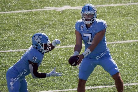North Carolina quarterback Sam Howell (7) hands off the ball to running back Michael Carter (8) during the first half of an NCAA college football game against North Carolina State in Chapel Hill, N.C