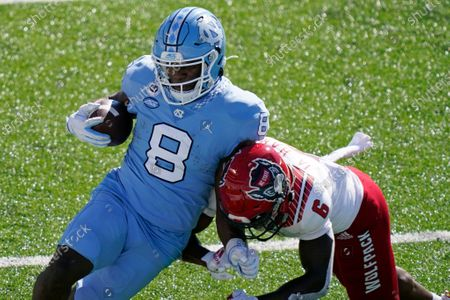 North Carolina running back Michael Carter (8) runs the ball while North Carolina State safety Jakeen Harris (6) makes the hit during the first half of an NCAA college football game in Chapel Hill, N.C