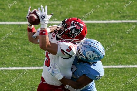 North Carolina State wide receiver Thayer Thomas (5) catches a pass while North Carolina defensive back Trey Morrison (4) defends during the second half of an NCAA college football game in Chapel Hill, N.C