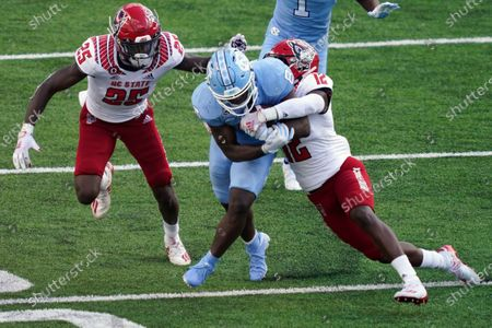 North Carolina running back Michael Carter (8) runs the ball while North Carolina State cornerback Shyheim Battle (25) and cornerback Devan Boykin (12) moves in for the tackle during the second half of an NCAA college football game in Chapel Hill, N.C