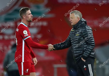 Sheffield United's manager Chris Wilder, right shakes hands with Liverpool's Jordan Henderson after the end of the English Premier League soccer match between Liverpool and Sheffield United at Anfield in Liverpool, England, . Liverpool won the match 2-1