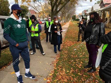 Milwaukee Bucks guard George Hill, left, speaks to LeRae Martin about the importance of voting on in Milwaukee. Hill and Bucks senior vice president Alex Lasry walked through various Milwaukee neighborhoods with volunteers from the Common Ground organization Saturday to remind residents to vote