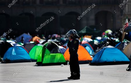 Police stands guard as people march in support of Mexico's President Andres Manuel Lopez Obrador on the perimeters of the Zocalo, the capital's main plaza, that is occupied by anti-government protesters who are demanding the resignation of the Mexican leader, in Mexico City
