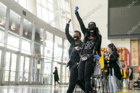 Sisters Debra Hubbard and Vanessa Howard raise their fists as they exit the Staples Center after casting their vote, as California in-person early voting for the U.S. Presidential election begins, in Los Angeles, California, USA, 24 October 2020. US President Donald J. Trump will face Democratic candidate Joe Biden in the US elections on 03 November.