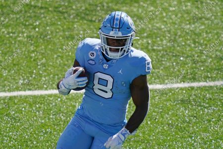 North Carolina running back Michael Carter (8) runs against North Carolina State during the first half of an NCAA college football game in Chapel Hill, N.C
