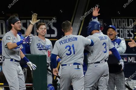 Los Angeles Dodgers' Chris Taylor celebrates at the dugout after scoring on a single by Corey Seager during the eighth inning in Game 4 of the baseball World Series against the Tampa Bay Rays, in Arlington, Texas
