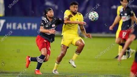 New England Revolution midfielder Lee Nguyen, left, and Nashville SC midfielder Anibal Godoy fight for the ball during the first half of an MLS soccer match, in Nashville, Tenn