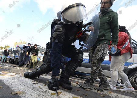 Polska policja w strojach bojowych zatrzymuje demonstrantów rozzloszczonych nowymi ograniczeniami majacymi na celu zwalczanie pandemii koronawirusa w Warszawie, w sobote 24 pazdziernika 2020 r. Wsród protestujacych byli przedsiebiorcy, skrajnie prawicowi politycy, kibice i przeciwnicy szczepionek. Protestujacy, wielu bez masek ochronnych, zlamali nowe ograniczenie dotyczace gromadzenia sie wiekszej liczby osób. Zatrzymania nastapily w zwiazku z rosnacymi napieciami spolecznymi, a nowe ograniczenia tuz przed calkowitym zamknieciem weszly w zycie w sobot